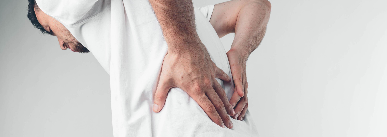Mann hält seinen rücken mit starken rückenschmerzen