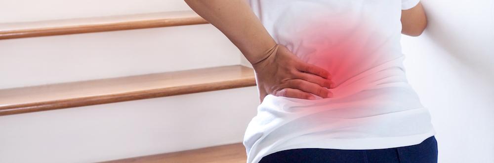 Frau geht Treppen auf hält sich den Rücken vor Schmerzen mit Wärmepflaster