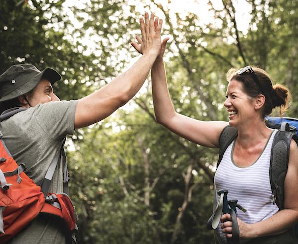 frau und mann wandern im wald high five aktive Bewegung gegen Kreuzschmerzen