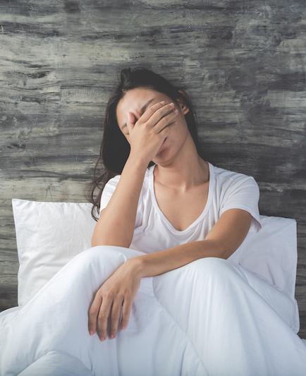 Frau mit Schlafstörungen im weißen Bett kann nicht einschlafen