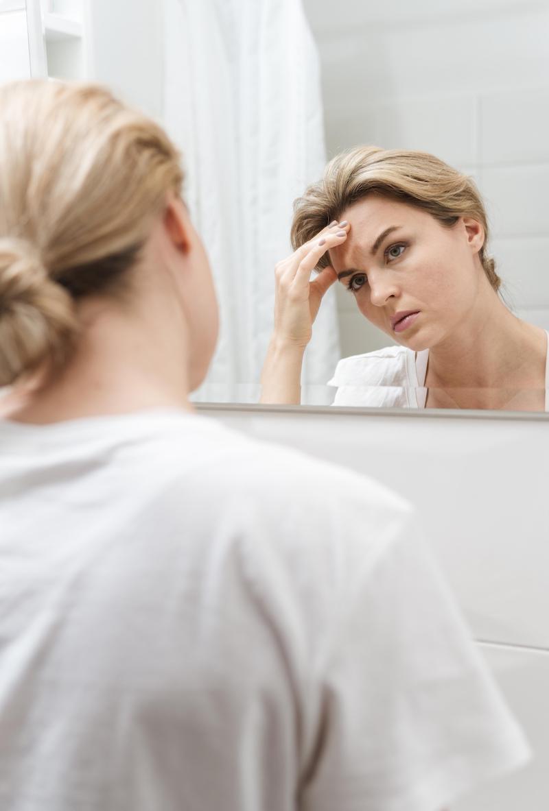 Frau frustriert vor Spiegel
