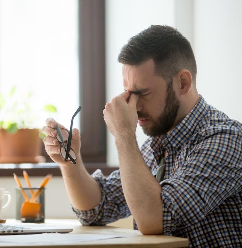 gestresster mann sitzt am Arbeitsplatz und leidet unter Kopfschmerzen
