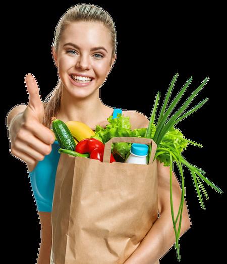 Junge Frau hält gesundes Essen in Papiertüte im Arm