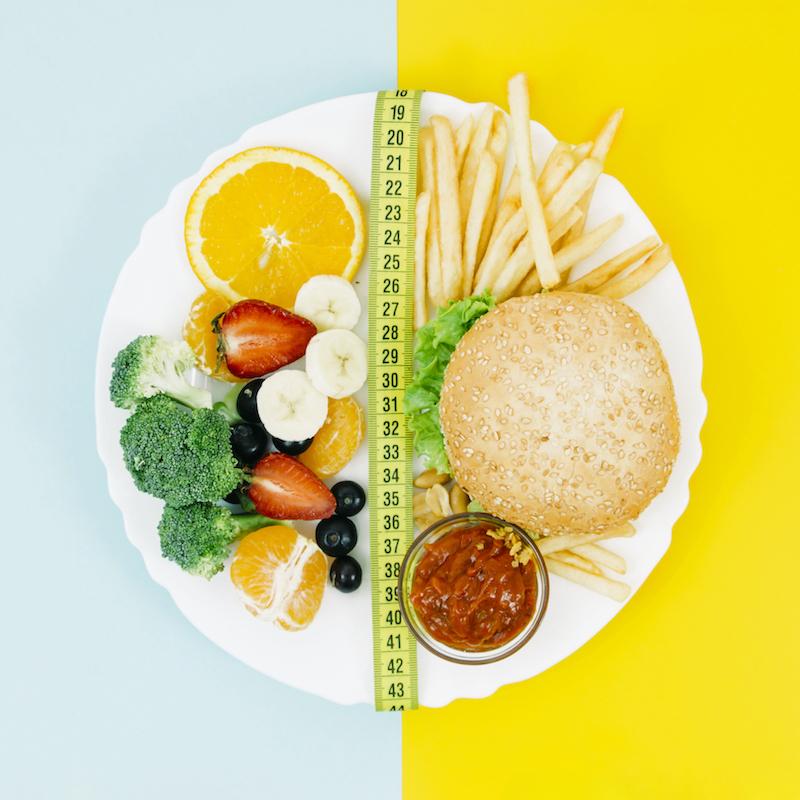 Teller mit Maßband getrennt mit gesundem und ungesundem Essen