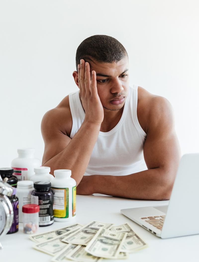 Junger Mann sitzt verzweifelt am Computer und scheitert an Muskelaufbau