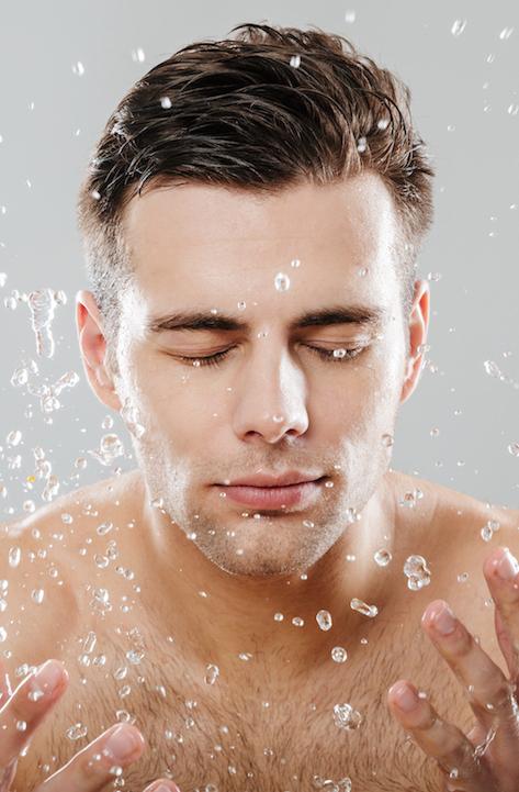 Junger Mann beim Gesicht Waschen gegen Pickel
