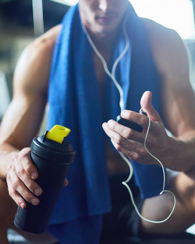 Erschöpfter Mann macht eine Pause beim Muskelaufbau Training
