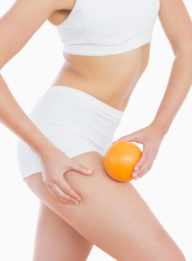 Frau vor weißem Hintergrund hält Orange am Bein