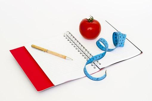 Maßband und Notizblock zur Protokollierung der Diät