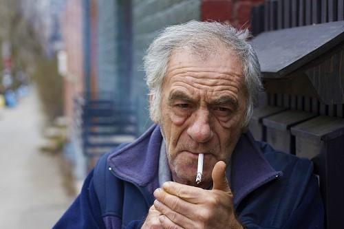 Alter Mann zündet sich eine Zigarette an