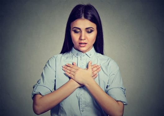 Frau fasst sich an die obere Brust, da Symptome einer COPD-Erkrankung auftreten