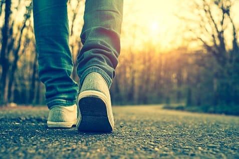 Mann läuft im Park spazieren, weil er seinen Stoffwechsel ankurbeln will