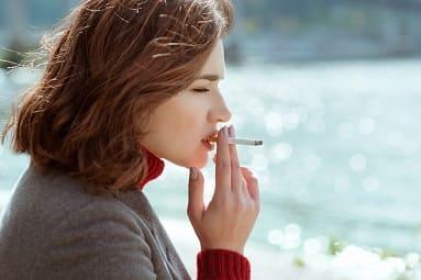 Frau kennt die Vorteile vom Rauchen aufhören, weiß aber nicht wie sie den Entzug schaffen kann und raucht aus Frust eine Zigarette