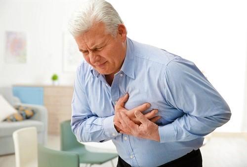 Mann greift sich an die Brust und spürt die Folgen des Rauchens