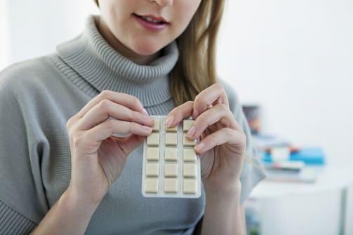 Frau öffnet Nikotinkaugummi-Verpackung