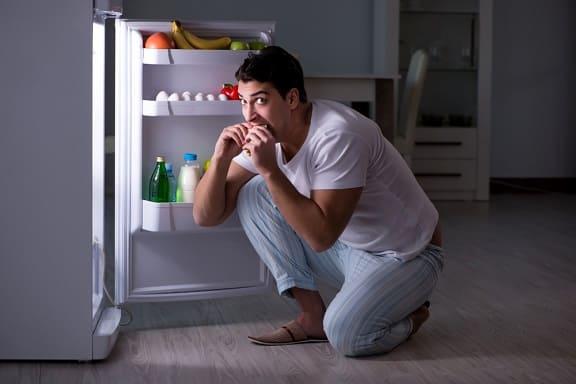 Mann hat Hungerattacken und bedient sich vom Kühlschrank