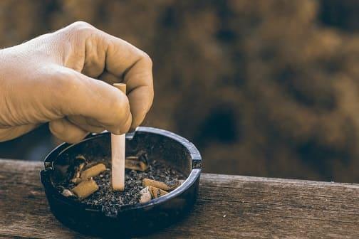 Mann drückt Zigarette im Aschenbecher aus