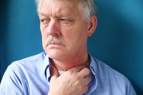 Mann hat Atemwegsreizungen und fasst sich an den Hals