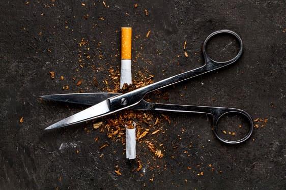 Eine Schere zerschneidet eine Zigarette