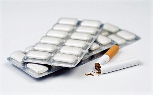Packung Nikotinkaugummis neben einer Zigarette, die schädlich ist