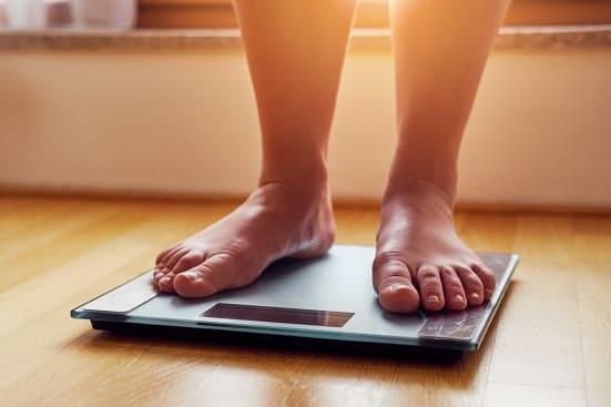Mann hat Angst vor einer Gewichtszunahme und wiegt sich auf einer Waage