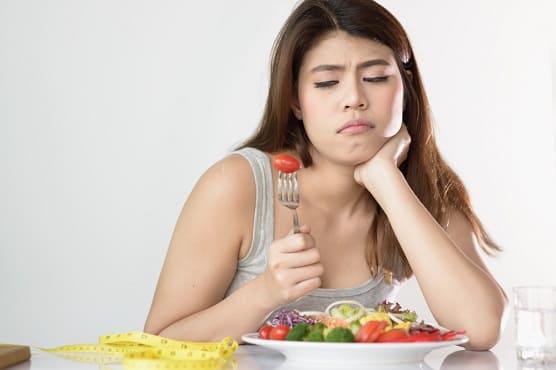 Frau macht eine Diät ist unglücklich über ihre Salatmahlzeit