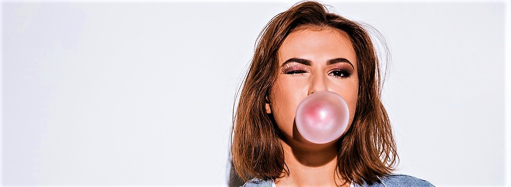 Frau blast eine Kaugummiblase