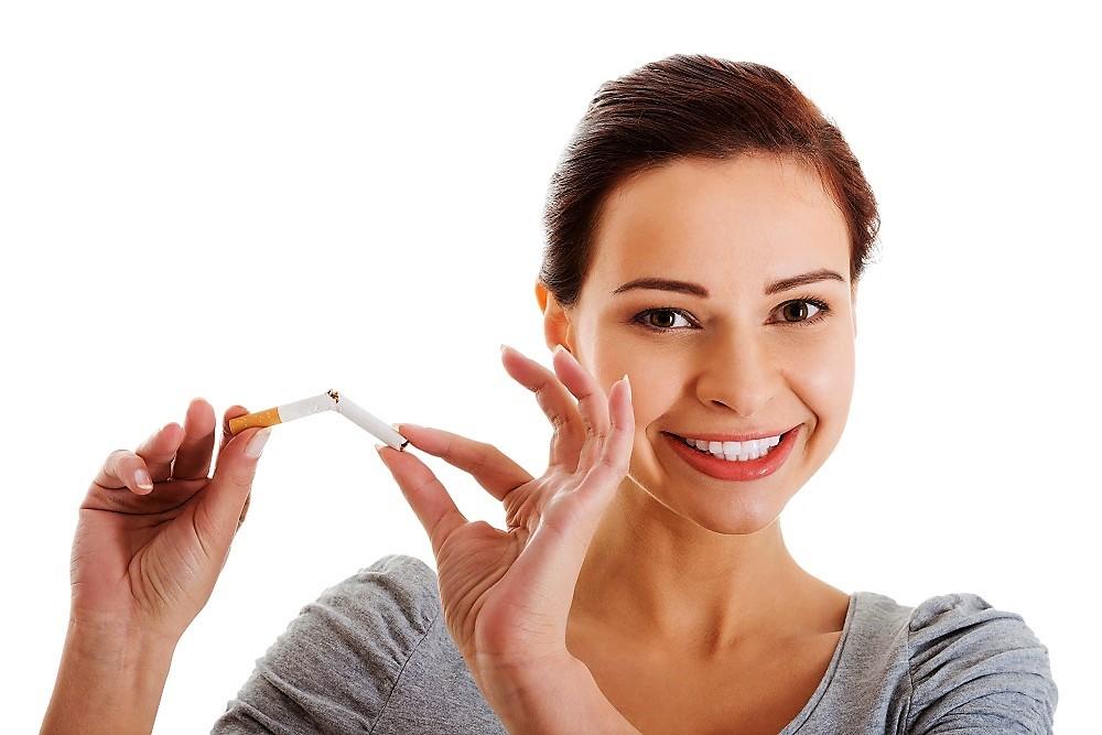 Frau zerbricht Zigarette, da sie mit dem Rauchen aufhören konnte