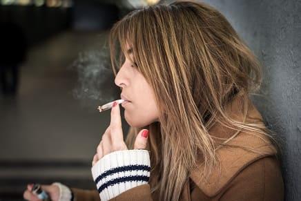Junge Frau raucht eine Zigarette