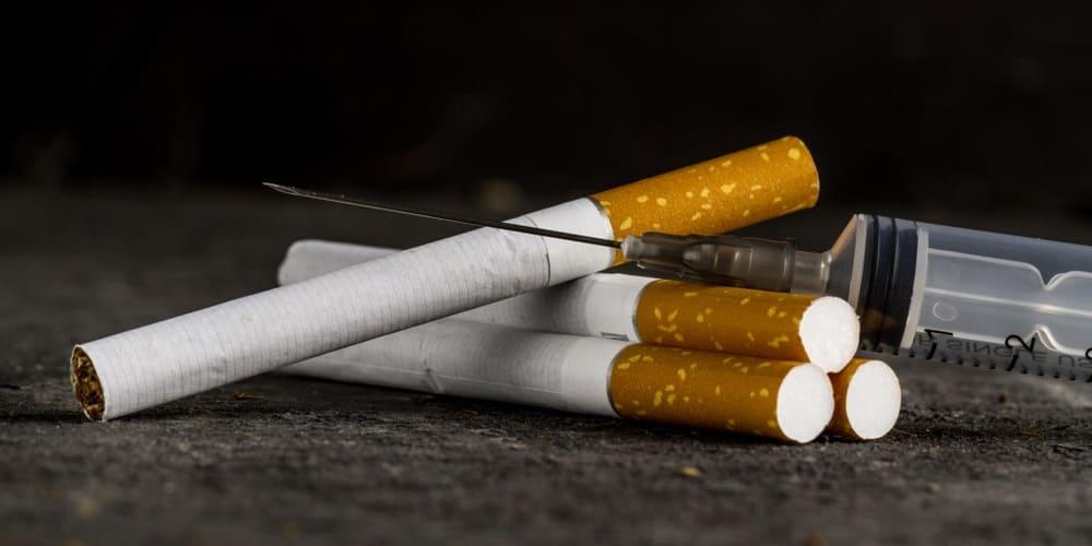 Rauchfreispritze liegt neben Zigaretten