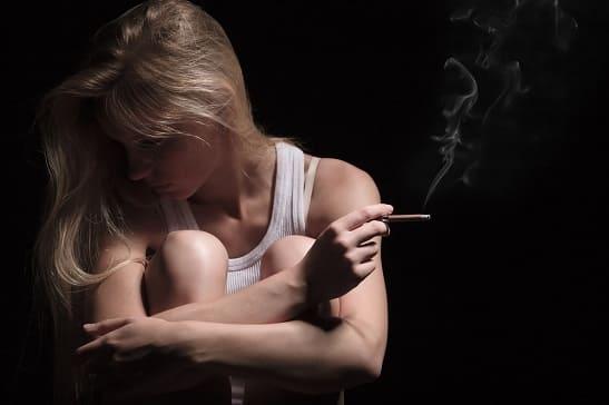Verzweifelte Frau raucht eine Zigarette nach langer Abstinenz