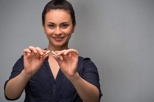 Frau zerbricht Zigarette, weil sie ihre Zähne aufhellen will