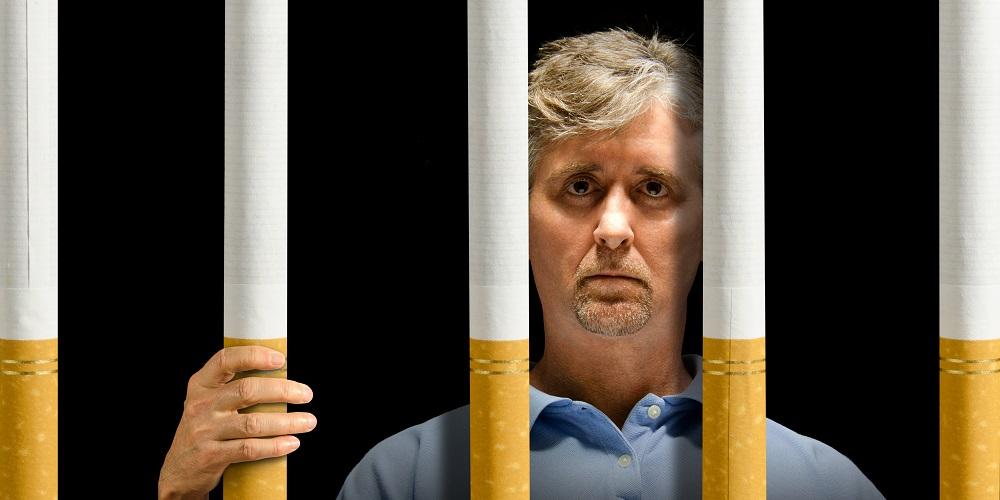Trauriger Mann ist in einer Gefängniszelle und die Gitter sind übergroße Zigaretten