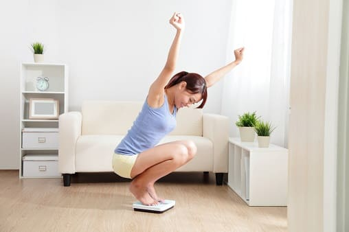 Frau wiegt sich und ist froh, weil die negativen Folgen des Rauchstopps bei ihr ausbleiben