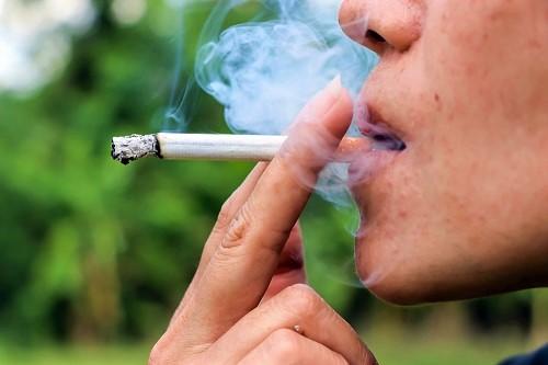 Mann raucht Zigarette und schmälert die Chance, gelbe Zähne wieder weiß zu bekommen