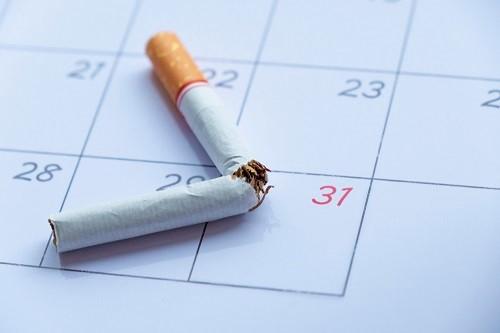 Zigarette liegt angebrochen auf einem Kalender