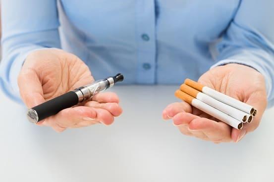 Man hält auf der linken Hand Zigaretten und auf der rechten eine E-Zigarette und fragt sich wie schädlich das Dampfen tatsächlich ist.