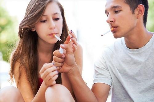 Freund zündet seiner Freundin die Zigarette an