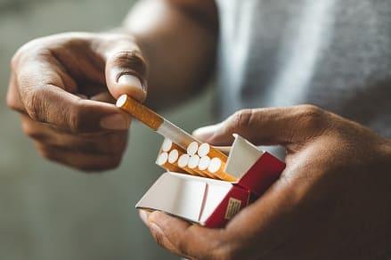 Mann hält die Nikotinabstinenz auf Dauer nicht aus und nimmt sich eine Zigarette aus der Schachtel
