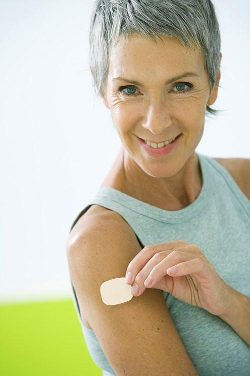 Frau klebt sich ein Nikotinpflaster auf
