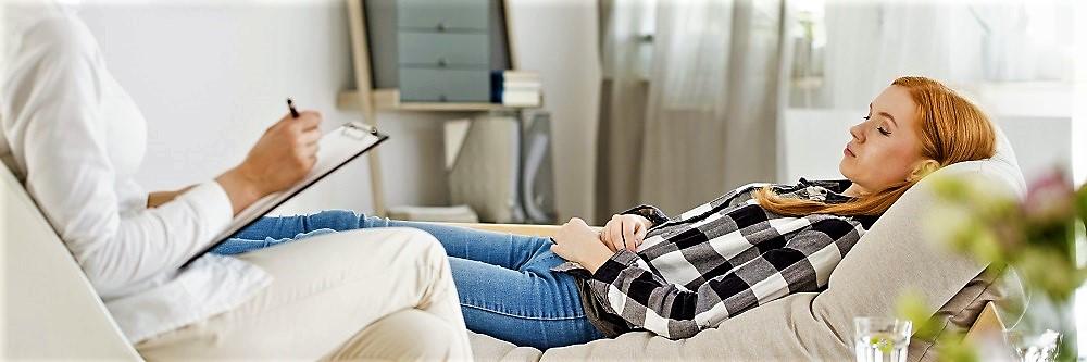 Frau sitzt auf Behandlungstisch und probiert eine Raucherentwöhnung durch Hypnose