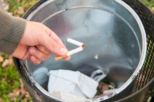 Mann wirft Zigarette in den Müll