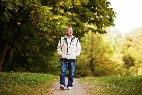 Mann läuft durch den Park, um seine körpereigene Regeneration zu fördern