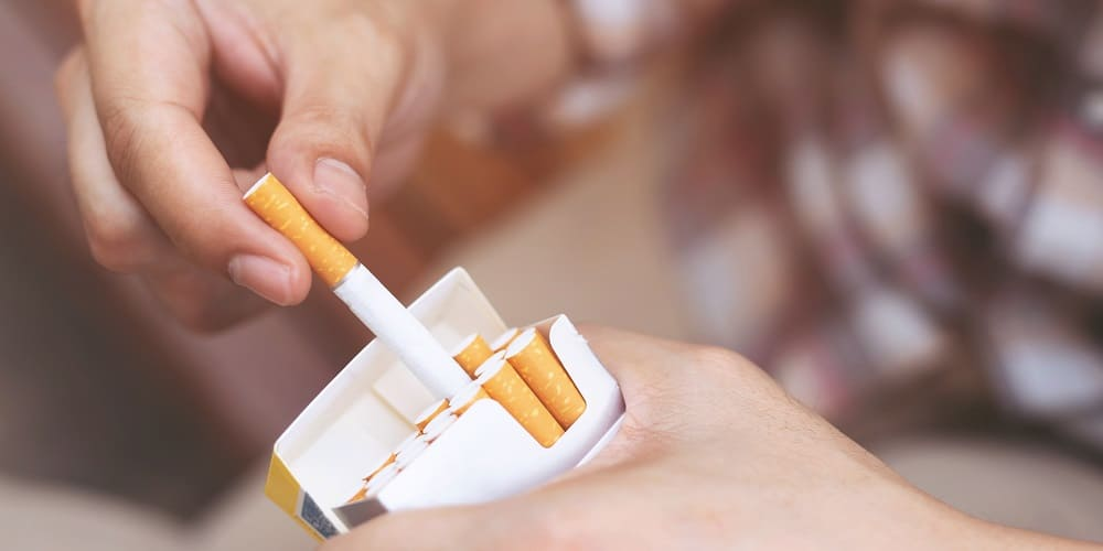 Mann holt aus einer Zigarettenschachtel eine Zigarette hervor