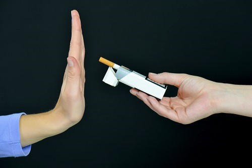 Frau leht Zigarette ab