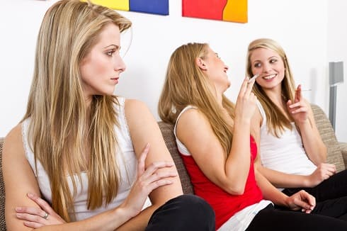 Frau sitzt neben ihren rauchenden Freundinnen, verzichtet jedoch selbst auf das Rauchen
