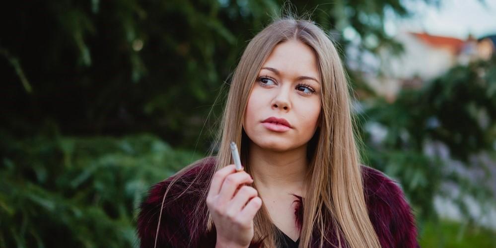 Junge Frau fragt sich, was wohl passiert, wenn man raucht