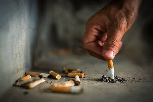 Mann drückt Zigarette aus, um endlich Nichtraucher werden zu können