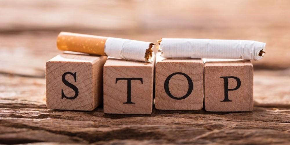 """Zerbrochene Zigarette liegt auf Holzwürfel mit der Aufschrift """"Stop"""""""
