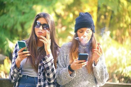 Junge Frauen rauchen und tippen am Smartphone